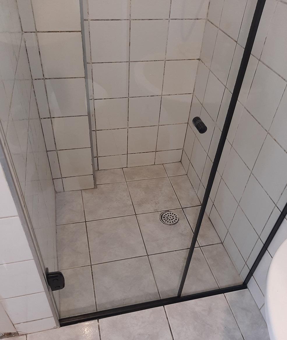 box de abrir vidro incolor com acabamento preto. vidro temperado de 8 mm, com modelo de fixação na parede lateral.