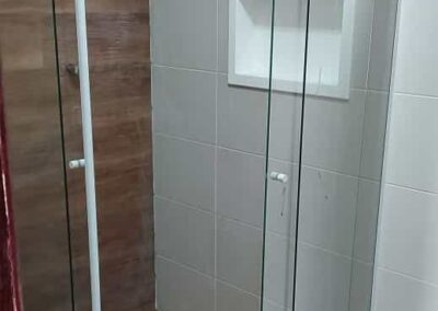 Box para banheiro modelo de canto vidro incolor com acabamento em alumínio branco.
